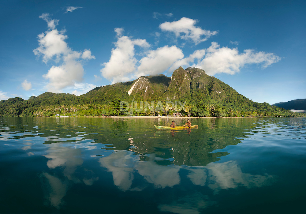 Panorama of boys fishing in front of Lobo Village. Mount Emensiri is reflected in water.