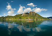 Panorama of boys fishing in front of Lobo Village. Mount Emensiri is reflected in water.