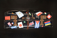 Suitcase with various flag stickers studio shot