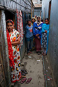 Ruma Akhter (far right with folded arms in blue sari) lives with her family of six in a rented 10-foot-by-10-foot square room in Dhaka, Bangladesh, where they share a communal kitchen and latrines with 8 other families.  (Ruma Akhter is featured in the book What I Eat: Around the World in 80 Diets.) MODEL RELEASED.