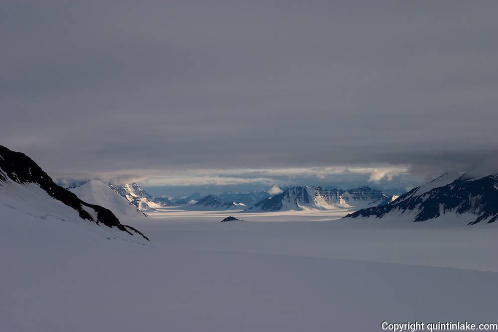 A glacier and jagged mountains seen from the edge of the Greenland ice cap during a British mountaineering expedition to Knud Rasmussens Land, East Greenland, Arctic, 2006.