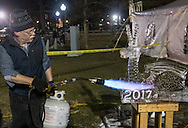 Goshen, New York - Professional ice sculptor Bill Bywater puts the finishing touches on an ice dragon during the Illuminate Goshen New Year's Eve Ball Drop on Dec. 31, 2016.