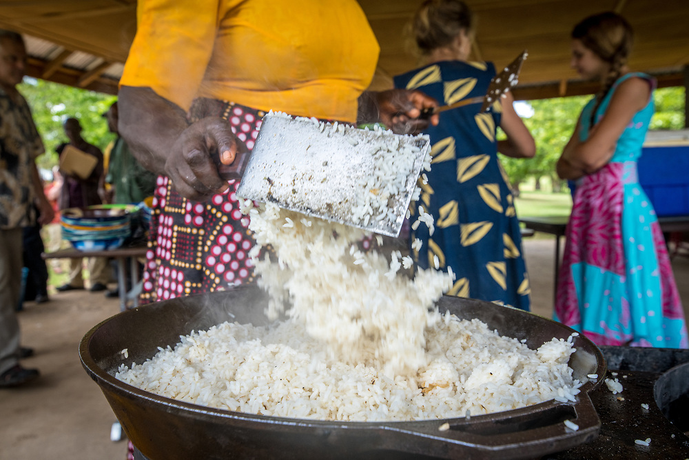 Rice((Oryza glaberrima) is tossed in a pot by a woman in Ganta, Liberia