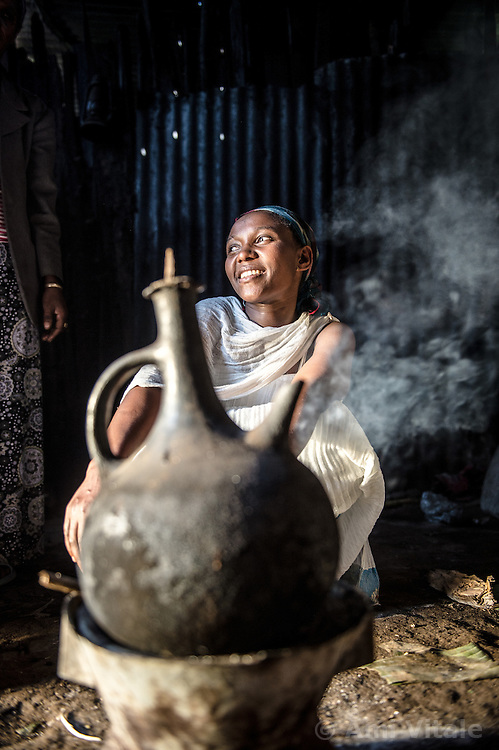 Amlel Ambaye prepares a coffee ceremony inside her family home near the Teppi plantation in the Kaffa region of Ethiopia.  Coffee permeates the cultural fabric of Ethiopian life, and is celebrated daily in coffee ceremonies. First she roasts the coffee beans over coals, then takes a mortar and pestle to grind, and a clay pot to boil and brew. Ethiopia is one of only two producing countries that drink more than half of what they grow.