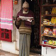 Man leest krant 's ochtends vroeg, Varanasi, India