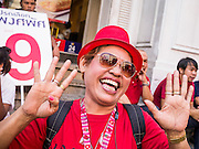 17 FEBRUARY 2013 - BANGKOK, THAILAND: A supporter of Pongsapat Pongchareon flashes the number 9 during a Pongsapat campaign rally. Nine is Pongsapat's number on the ballot. Pol General Pongsapat Pongcharoen, a former deputy national police chief who also served as secretary-general of the Narcotics Control Board is the Pheu Thai Party candidate in the upcoming Bangkok governor's election. (He resigned from the police force to run for Governor.) Former Prime Minister Thaksin Shinawatra reportedly recruited Pongsapat. Most of Thailand's reputable polls have reported that Pongsapat is leading in the race and likely to defeat Sukhumbhand Paribatra, the Thai Democrats' candidate and incumbent. The loss of Bangkok would be a serious blow to the Democrats, whose base is the Bangkok area.      PHOTO BY JACK KURTZ
