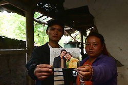 59601373  .The 31-year-old Su Kaifeng (L) and his 26-year-old wife Luo Junxiu pose for photo with an old picture of them in the quake-hit Longmen Village, southwest China s Sichuan Province, May 4, 2013. The old picture was taken at a temple fair in the winter of 2008. Old photos are not daily necessities for who just suffered a 7-magnitude earthquake, but they are still cherished as they recorded peoples past life and recalled memories, May 4, 2013.  Photo by: i-Images.UK ONLY