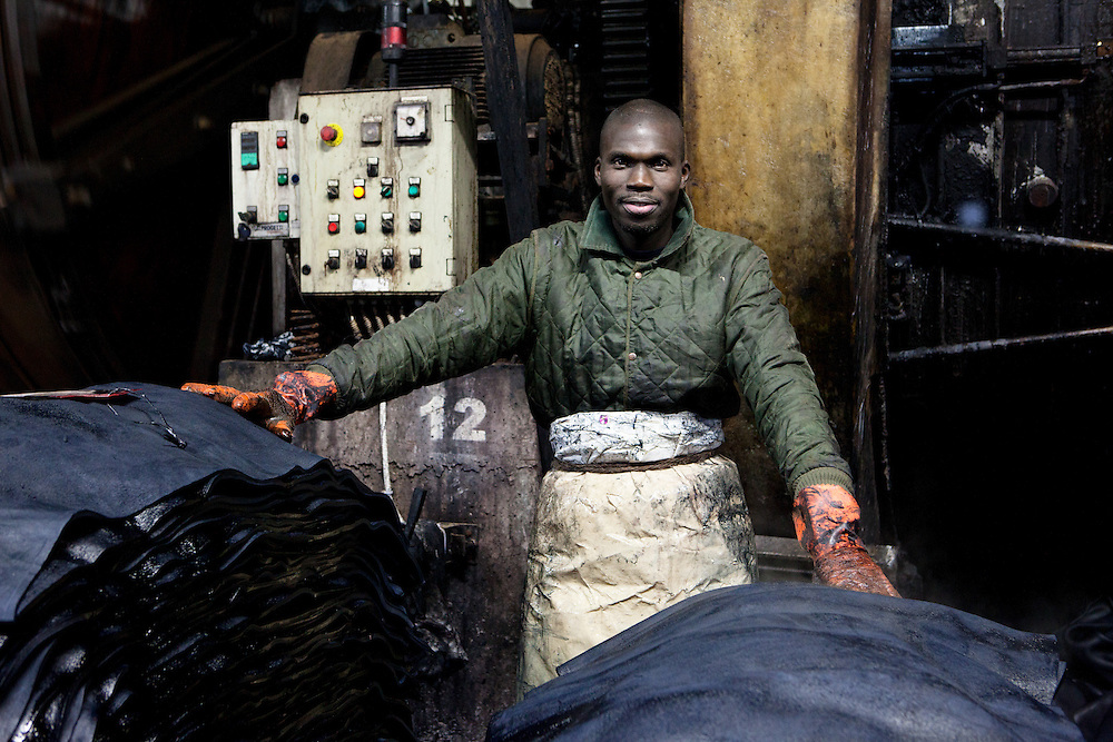 Santa Croce Sull'Arno, Italy. Bonistalli & Stefanelli SPA, hides and skins tanning. .Portrait of a worker near a pile of black colored leather.