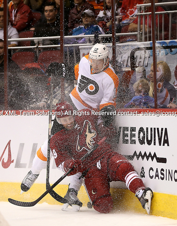 29 December 2014: Arizona Coyotes center Sam Gagner #9 is hit by Philadelphia Flyers left wing Michael Raffl #12 during the first period of the NHL regular season game between the Philadelphia Flyers and the Arizona Coyotes at Gila River Arena in Glendale, Az.