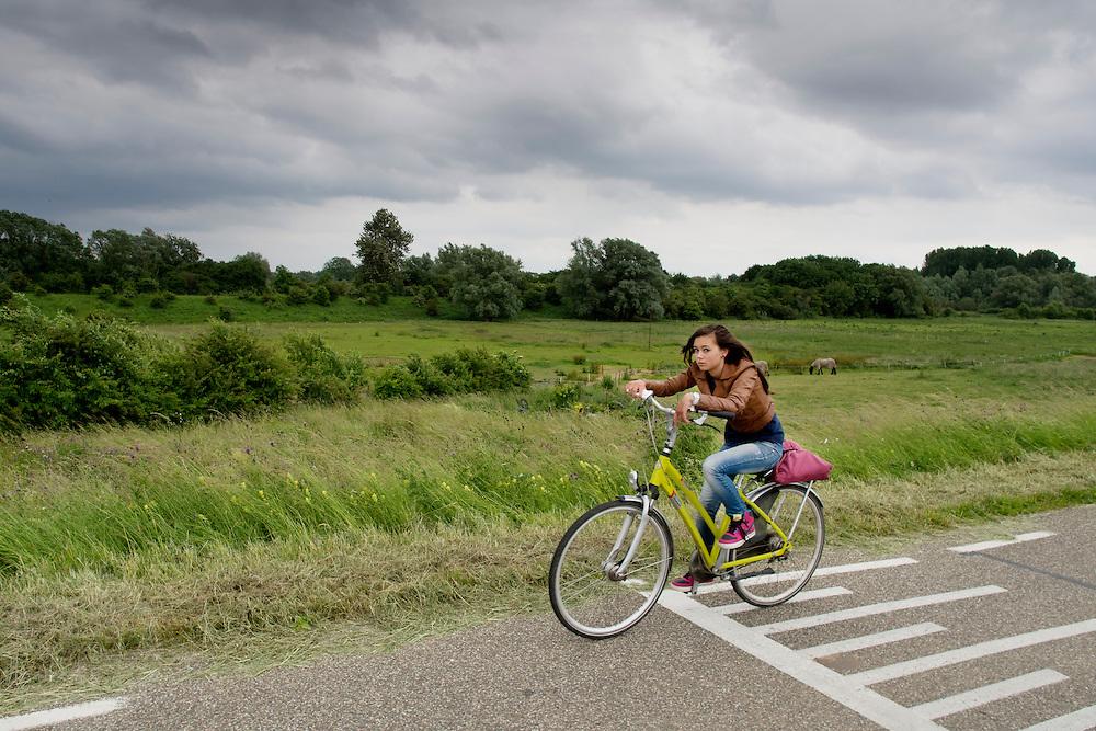Een eenzame scholier op de fiets op de dijk in de Ooijpolder bij Nijmegen.<br /> <br /> A lonely pupil cycling on a dike in the Ooijpolder near Nijmegen.