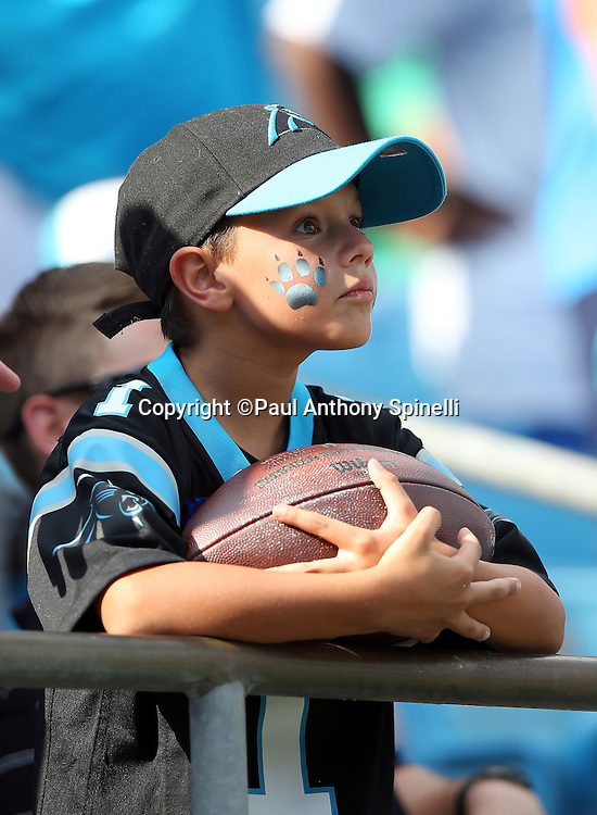 A young Carolina Panthers fan with a painted face holds a football given to him by Carolina Panthers quarterback Cam Newton (1) during the Carolina Panthers 2015 NFL week 2 regular season football game against the Houston Texans on Sunday, Sept. 20, 2015 in Charlotte, N.C. The Panthers won the game 24-17. (©Paul Anthony Spinelli)