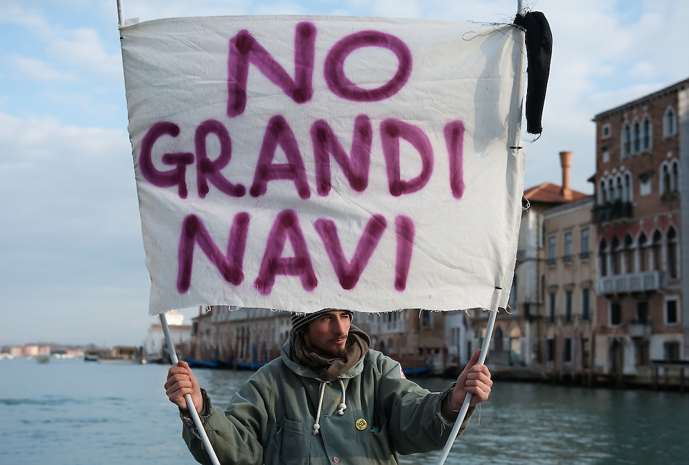 """VENICE, ITALY - JANUARY 16:  A protester sailing on the Grand Canal holds black listed banner reading """"Stop the large Ships""""  on the day of the special meeting discussing the environmental impact of cruises in Venice on January 16, 2012 in Venice, Italy. Protest are mounting in Venice against large cruise ships crossing St Marks's basin after the Costa Concordia tragedy."""