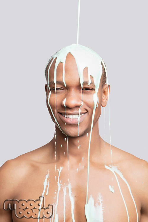 Portrait of shirtless young man with paint falling on his head against gray background