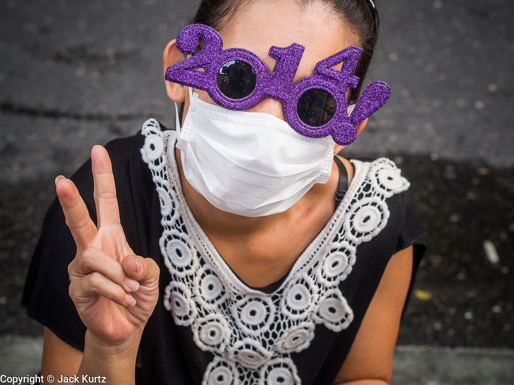 31 DECEMBER 2013 - BANGKOK, THAILAND:   A woman sells 2014 sunglasses on New Year's Eve in Bangkok. Hundreds of thousands of people pack into the Ratchaprasong Intersection in Bangkok for the city's annual New Year's Eve countdown. Many Thais go the Erawan Shrine and Wat Pathum Wanaram near the intersection to pray and make merit.   PHOTO BY JACK KURTZ