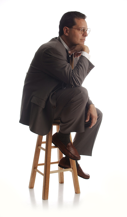business executive thinking on stool