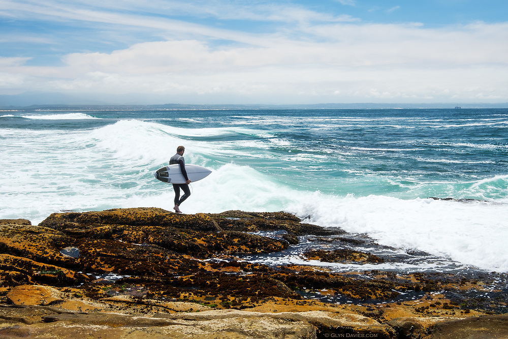 A surfer spends quite some time calculating how to throw himself into the powerful waves of the Indian Ocean at Mossel Bay in South Africa