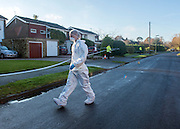 © Licensed to London News Pictures. 27/11/2014. Fetcham, UK. Forensic officers at the scene with the house in the background (white garage door) .  A manhunt is under way across two counties after a man and woman were found stabbed to death in Surrey. The bodies were found at a house in Fetcham, near Leatherhead, after Surrey Police were alerted in the early hours.. Photo credit : Stephen Simpson/LNP
