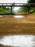 01 JULY 2015 - NON PHAK NAK, SUPHAN BURI, THAILAND:  People ride their motorcycles over an empty irrigation canal in Lopburi province. Normally the canal is completely full at this time of year. Central Thailand is contending with drought. By one estimate, about 80 percent of Thailand's agricultural land is in drought like conditions and farmers have been told to stop planting new acreage of rice, the area's principal cash crop. Water in reservoirs are below 10 percent of their capacity, a record low. Water in some reservoirs is so low, water no longer flows through the slipways and instead has to be pumped out of the reservoir into irrigation canals. Farmers who have planted their rice crops are pumping water out of the irrigation canals in effort to save their crops. Homes have collapsed in some communities on the Chao Phraya River, the main water source for central Thailand, because water levels are so low the now exposed embankment is collapsing. This is normally the start of the rainy season, but so far there hasn't been any significant rain.    PHOTO BY JACK KURTZ