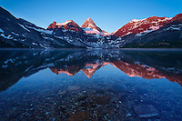 Intense Alpen Glow colours Canada's spectaculary symmetrical Mt. Assiniboine, as the underlying rocks show through for a brief moment before the wind picks up again.