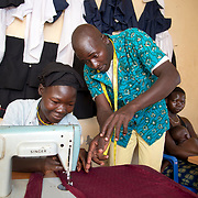 Uganda . Adjumani. Olanya Sunday, tailor.  He now trains two people in his shop. He has epilepsy and a son with epilepsy. Here he is teaching  Joyce Mesiku.