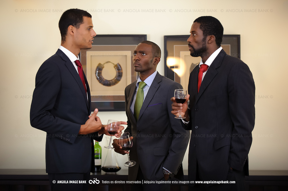 Três senhores a conversarem sobre negócios numa sala de estar. Angola