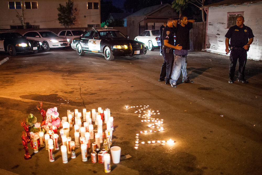 Members of Stockton's Community Response Team pat down an individual at the site of a memorial for five people shot the night before in Stockton, California, September 18, 2013. Facing stark and rising homicide rates, the California cities Oakland and Stockton are taking a second chance at a novel method of disrupting street gangs, called Ceasefire, in which the police use social-analytics software to map out connections between a city's most violent gang members, using the data to make targeted and coordinated arrests.