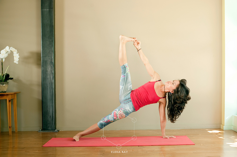 Fit woman in her mid 40's in the yoga pose Vasisthasana while practicing in the yoga studio.
