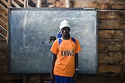 "Maombi, 15, stands in front of the blackboard in a classroom at the Angalisho adventist primary school in Goma, Eastern DRC, on Sunday December 14, 2008. ""When I finish school, I want to become a teacher, I want to be someone in life,"" she says. Maombi and her family found shelter the school when they arrived in Goma after conflict forced them out of their home in Burumba, 12km from Goma. Every morning, they vacate the classroom to allow children to attend school, and come back in the afternoon. ""I feel uncomfortable living here. I sleep on stones, i dont eat well. I like to go to school, now I do nothing,"" says Maombi. ""I'm jealous to see other children go to school."""