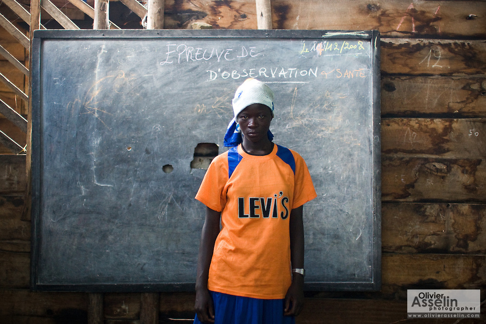 """Maombi, 15, stands in front of the blackboard in a classroom at the Angalisho adventist primary school in Goma, Eastern DRC, on Sunday December 14, 2008. """"When I finish school, I want to become a teacher, I want to be someone in life,"""" she says. Maombi and her family found shelter the school when they arrived in Goma after conflict forced them out of their home in Burumba, 12km from Goma. Every morning, they vacate the classroom to allow children to attend school, and come back in the afternoon. """"I feel uncomfortable living here. I sleep on stones, i dont eat well. I like to go to school, now I do nothing,"""" says Maombi. """"I'm jealous to see other children go to school."""""""