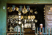 A Muslim brass vendor waits in his shop outside Zamboanga City, Mindanao, Philippines