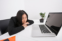 Bored businesswoman looking at laptop in office
