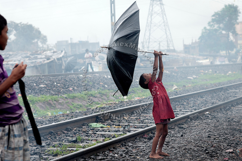 On a rainy day, a girl is playing with an umbrella along the railway tracks passing through New Arif Nagar, one of the water-affected colonies surrounding the abandoned Union Carbide (now DOW Chemical) industrial complex in Bhopal, Madhya Pradesh, India.