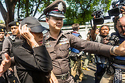 "01 FEBRUARY 2014 - BANGKOK, THAILAND: A Thai police officer helps an anti-government worker get away from a mob of voters upset that they couldn't vote because she and other protestors blocked access to the polls. Thais went to the polls in a ""snap election"" Sunday called in December after Prime Minister Yingluck Shinawatra dissolved the parliament in the face of large anti-government protests in Bangkok. The anti-government opposition, led by the People's Democratic Reform Committee (PDRC), called for a boycott of the election and threatened to disrupt voting. Many polling places in Bangkok were closed by protestors who blocked access to the polls or distribution of ballots. The result of the election are likely to be contested in the Thai Constitutional Court and may be invalidated because there won't be quorum in the Thai parliament.    PHOTO BY JACK KURTZ"