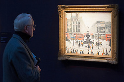 "© Licensed to London News Pictures. 21/03/2014. London, UK. A visitor to Sotheby's auction house views ""Piccadilly Circus"" (1959) (est. GB£2000,000-3,000,000) by British artist LS Lowry during the press view for a new sale of the artist's work in London today (21/03/2014). The auction, entitled ""Lowry: The AJ Thompson Collection"", features works by Lowry assembled over a 30 year period by collector A.J. Thompson. Photo credit: Matt Cetti-Roberts/LNP"