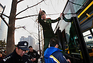 A Chinese paramilitary Police helps Chinese police clear the scene where petitioners threw written accounts of their grievances near Tiananmen square, in hopes to have their case seen and heard by a larger audience, after failed attempts to have their cases heard at the Petition's office  in  Beijing, China, Tuesday, March 3, 2009. Many Chinese have come from around the country to Beijing seeking redress for problems with local officials, flocking to the capital to coincide with the annual National People's Congress session. Their numbers commonly increase ahead of the meeting, and they are often followed by local police to the capital and taken back home.