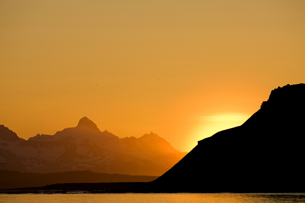 USA, Alaska, Katmai National Park, Morning sun lights mountain peaks along Hallo Bay