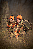 MALE AND FEMALE DEER HUNTERS WEARING BLAZE ORANGE WHILE RATTLING FOR DEER AND USING A RIFLE