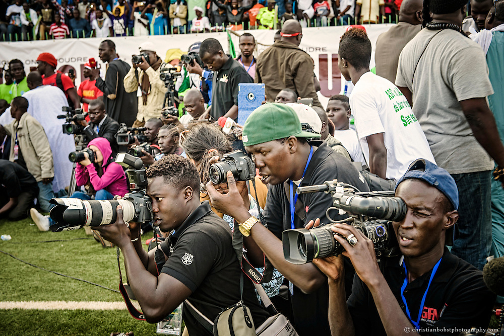 Senegalese Sport-photographers and cameramen compete for the best picture during the fight.