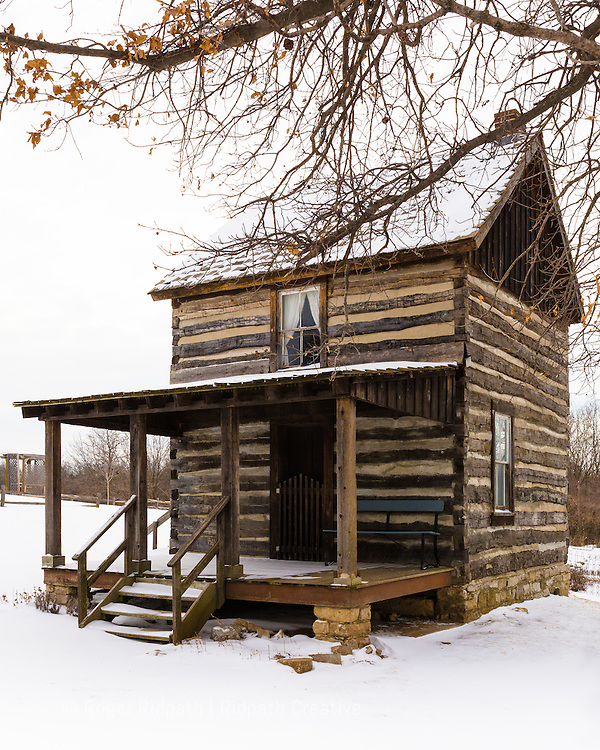 historic log cabin in snow Shoal Creek Living History Museum in Kansas City, Missouri