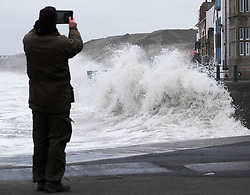 © Licensed to London News Pictures. <br /> 21/03/2015. <br /> <br /> Sandsend, North Yorkshire.<br /> <br /> A man takes a picture as a huge wave crashes against the sea wall at Sandsend in North Yorkshire. The exceptionally high Spring tides were created by the moon's 18-year cycle.<br /> <br /> Photo credit : Ian Forsyth/LNP