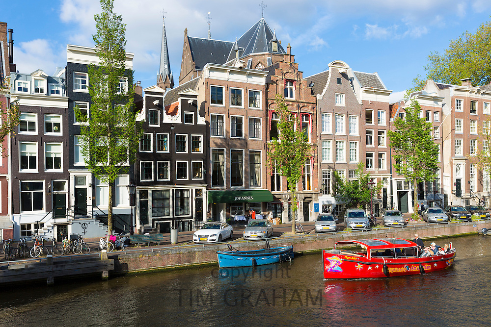 Tourists on canal sightseeing cruise boat trip pass Johannes Restaurant on canalside street, Herengracht, Amsterdam, Holland