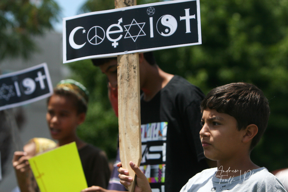 /Andrew Foulk/ For The Californian/ .Mohammed Qalla, 11, a supporter of the Temecula Islamic Center, holds signs during a protest staged by opponents of the centers plans to build a new mosque in Temecula.