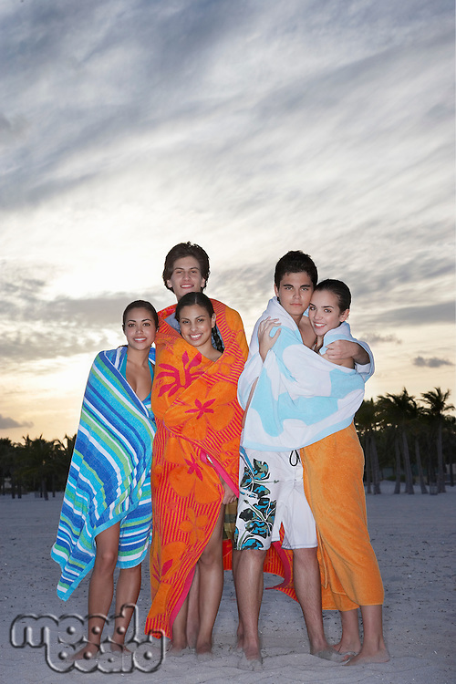 Teenagers (16-19) wrapped in towels on beach