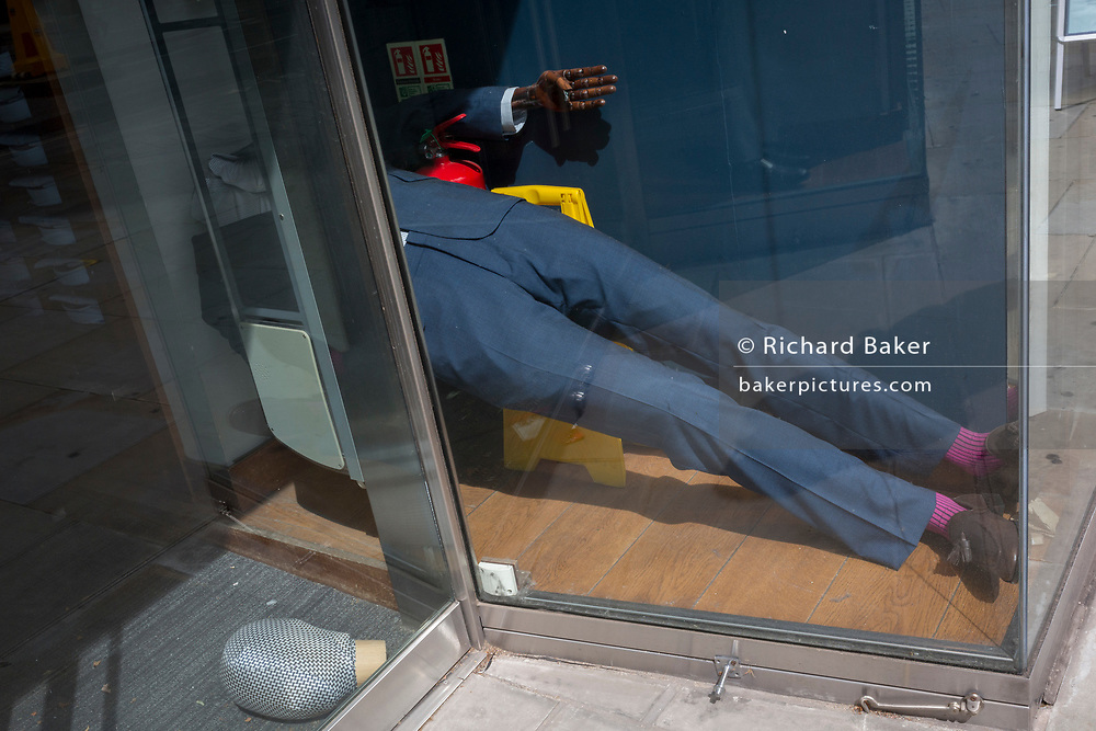 """After months of a menswear retailer's forced closure during the UK Coronavirus pandemc lockdown, one of its mannequins has fallen over on to the shop floor, its head lying by the door. The number of deaths from Coronavirus in the last 24hrs has increased by 287 to 37,979 while the government lowered the national Covid-19 alert level from 4 to 3, meaning the virus is considered to be """"in general circulation .. with """"a gradual reduction in restrictions"""", on 19th June 2020, in the City of London, England."""