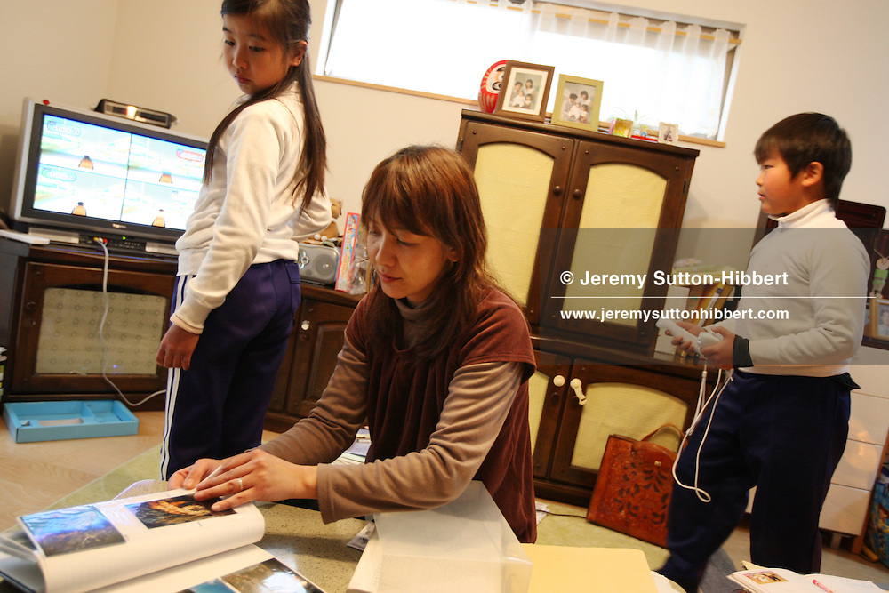 Hiroko Uchino (38yrs) with her daughter Ami (9 yrs) and son Yuki (7 yrs), in their home in Anjo city, Japan, Tuesday, January 29th 2008. Hiroko's husband Kenichi died aged 30 on 9th Feb 2002 of heart failure, whilst at work at Toyota Motor Company. His wife claims that in the month preceeding his death he worked 144 hours of overtime.