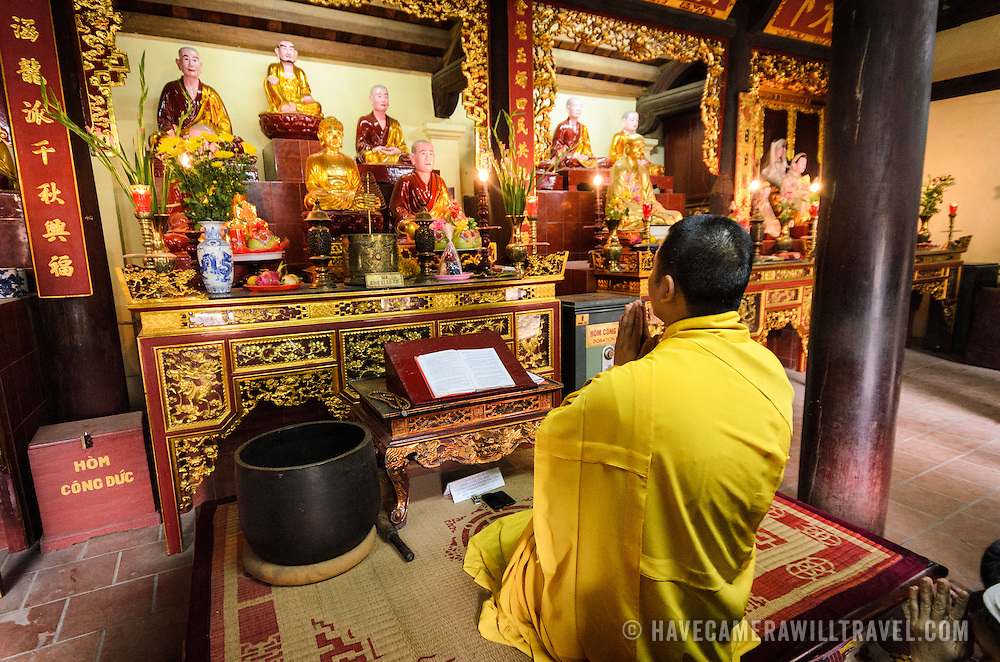 A Buddhist monk prays at the altar at Tran Quoc Pagoda on a small island on West Lake (Ho Tay). Originally built in the 6th century on the banks of the Red River, a changing course of the river forced the pagoda to be relocated in 1615 to Golden Fish (Kim Ngu) islet on the lake.