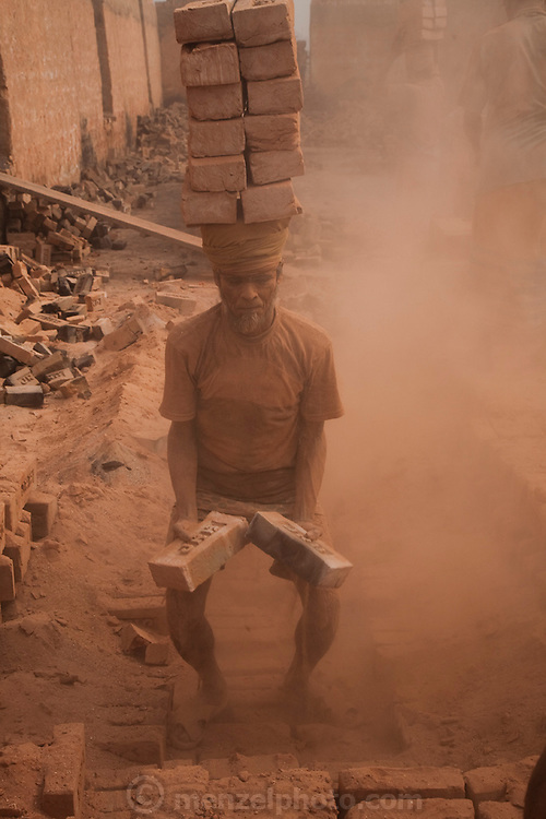 A man carries a stack of bricks at the JRB brick factory near Sonargaon, outside Dhaka, Bangladesh. The heavy clay soils along the river near the market town of Sonargaon are well suited for making bricks. At the JRB brick factory, workers of all ages move raw bricks from long, stacked rows, where they first dry in the sun, to the smoky coal-fired kilns. After being fired, the bricks turn red. A foreman keeps tally, handing the workers colored plastic tokens corresponding to the number of bricks they carry past him. They cash in the chips at the end of each shift, taking home the equivalent of $2 to $4 (USD) a day.