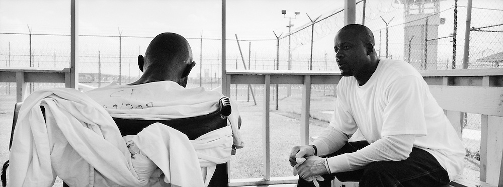 Felton Love, right, watches Timothy Minor closely in the hospital courtyard at Angola Prison. Love has volunteered to care for Minor, who is dying from a brain tumor. Minor has lost much of his muscle control. To enable Minor to sit up in his wheelchair, Love has wrapped him with bedsheets.