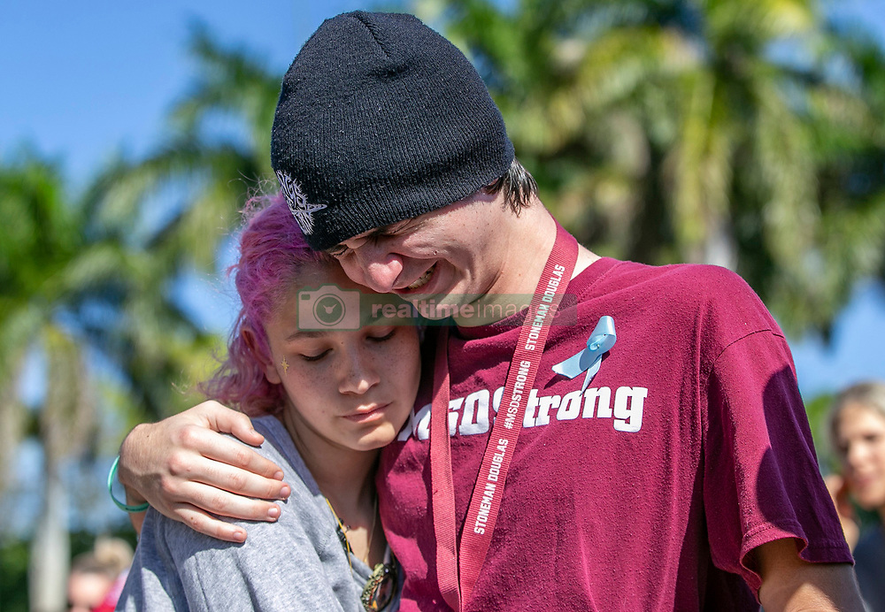 Marjory Stoneman Douglas High School students Victoria Gonzalez and Liam Kiernan embrace at a memorial in front of the school during the one year anniversary of the shooting deaths of 17 people in Parkland, FL, USA on Thursday, February 14, 2019. Photo by Al Diaz/Miami Herald/TNS/ABACAPRESS.COM