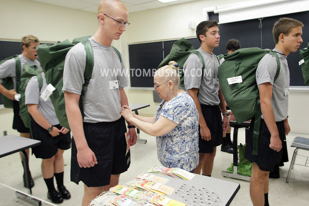 Cornelia Bambino, center, puts a company tag on a new Cadet during R-Day at the U.S. Military Academy at West Point on Monday, July 2, 2012.